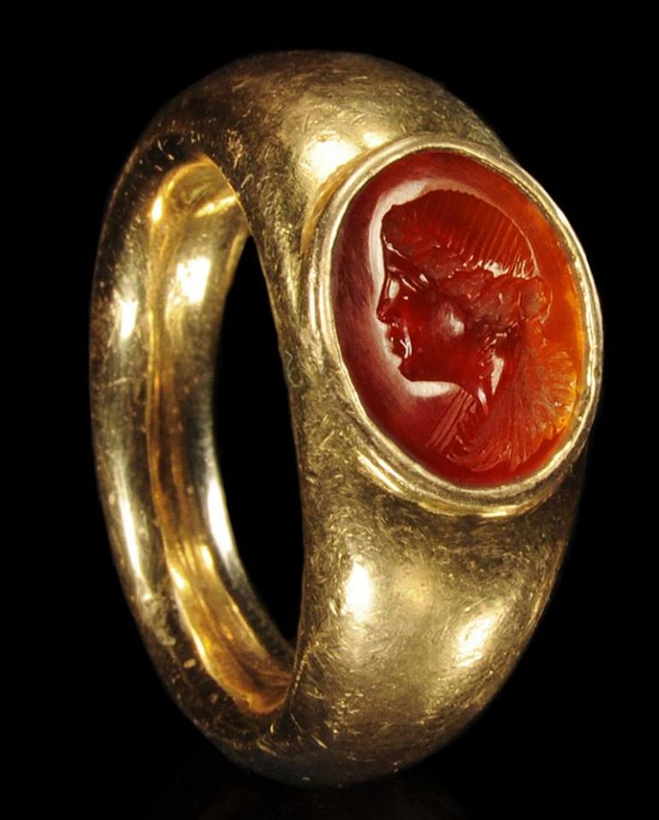 An ancient Roman gold ring set with a carnelian intaglio of a woman with braided locks of hair.