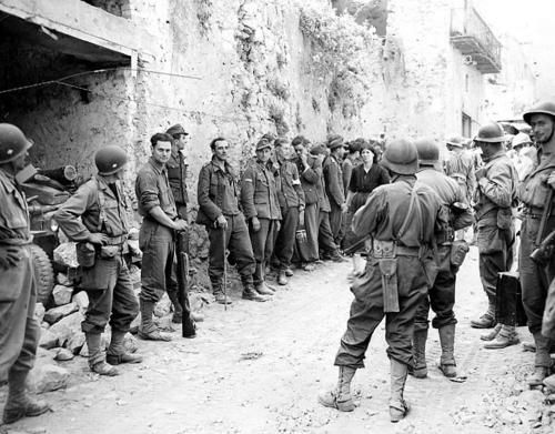 Soldiers of the French Expeditionary Corps (on the right), part of the U.S. 5th Army, guarding German prisoners of war on the street of an Italian town.