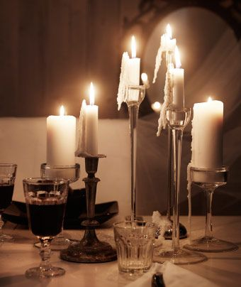 Lit white candles in different glass and metal candle holders