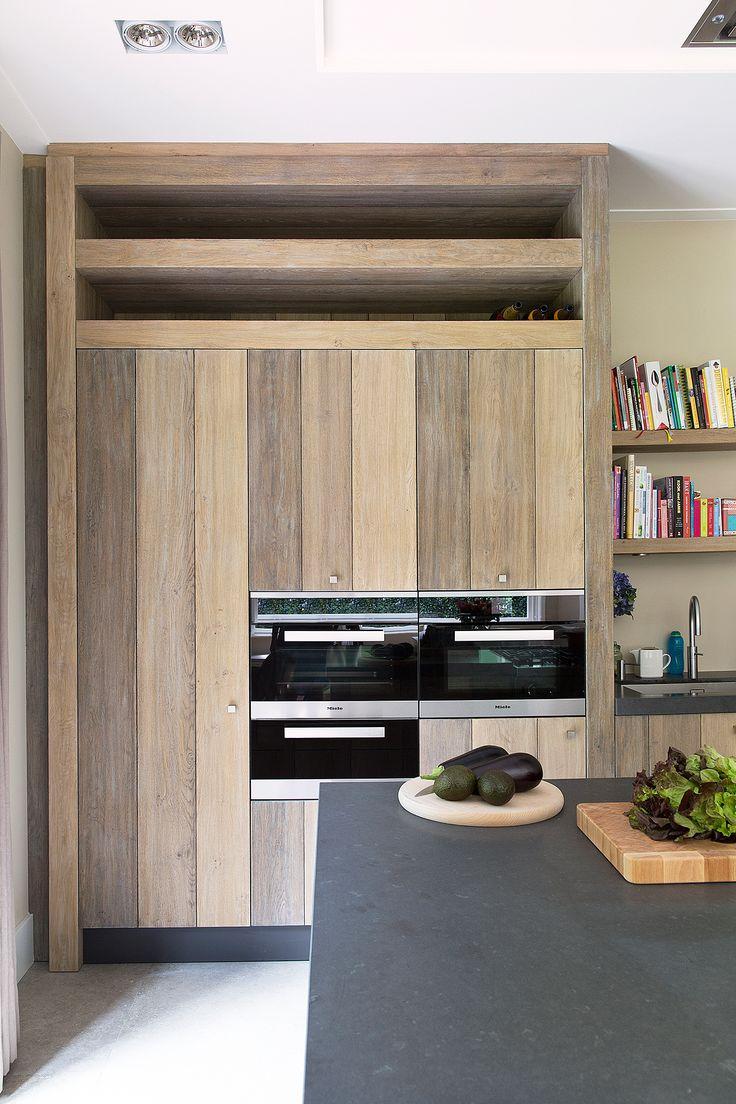 Keukenapparatuur ingebouwd in hoge houten keukenkast