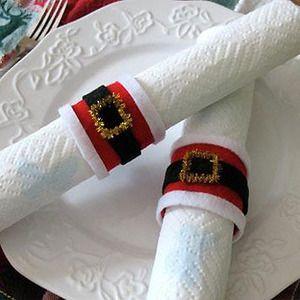 Anillos para servilletas con rollos de confort: Recortar los rollos de papel para que tengan el ancho de los servilleteros. Con ayuda del pegamento, pegar una huincha de paño lensi rojo rodeando el cartón. Corta una tira de paño lensi negro y pegalo sobre el rojo. Con un limpiapipas dorado, hacer un pequeño rectángulo para formar la hebilla de nuestro servilleter navideño. X