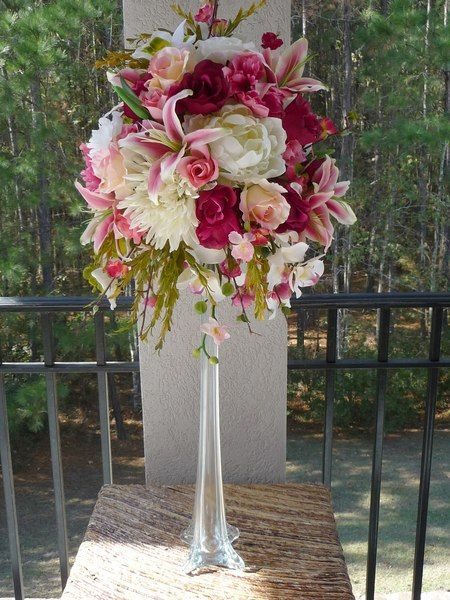 Fuchsia and cream floral centerpiece on a tower vase