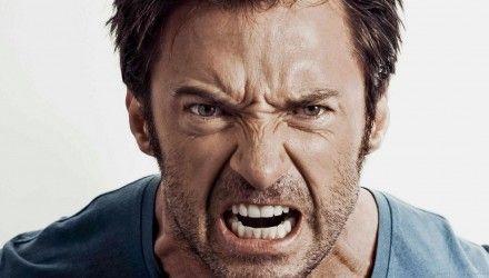 Homem irritado com camisa azul e barba mal feita com os dentes à mostra