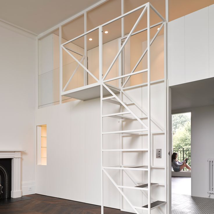 Wireframe staircase leads to mezzanine sleeping nest in west London flat renovation
