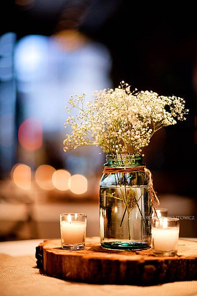 baby's breath, votive candles, simple jars, and a wood cookie.  perfect.