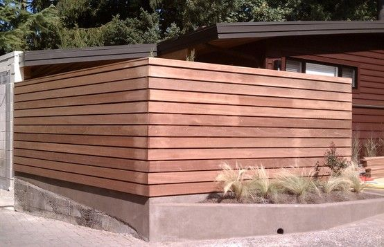 Modern wooden fence with cement base adds clean lines to