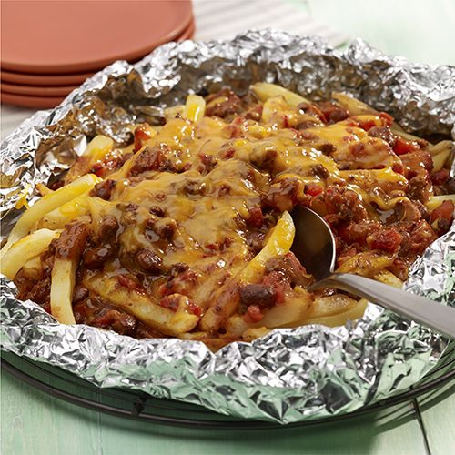 Fries topped with chili, diced tomatoes and cheese wrapped in foil for a grilled foil packet recipe to serve as an easy side with no messy dishes