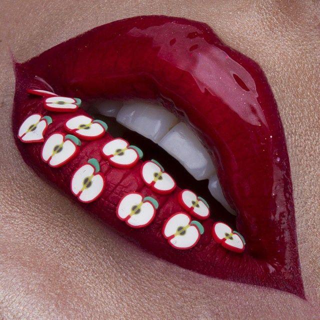 Labios pintados en color rojo con manzanas de adorno