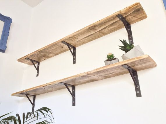 Add a touch of rustic class to your home with these reclaimed wood shelves with welded steel brackets.  Dimensions: Length 100cm / 39.5 Width 14cm / 5.5 Height 14cm / 5.5 (Shelf top to bracket base)  Includes 1 x Shelf, 3 x brackets, general purpose wall plugs and fixing screws.  Brackets are available in Natural Steel or Brilliant White powder-coated finish.  The wood is carefully sanded multiple times to achieve a smooth touch whilst retaining its aged character and texture. All edges are…