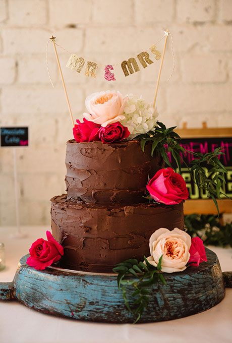A two-tiered chocolate wedding cake decorated with fresh flowers.