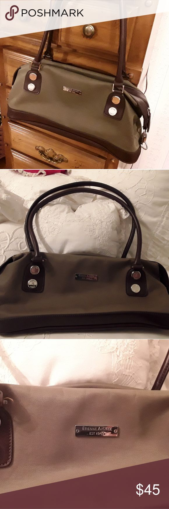 """NEW ETIENNE AIGNER HANDBAG BROWN /GREEN, 24"""" STRAP I HAVE FOR SALE A NEW ETIENNE AIGNER HANDBAG.  IT HAS BROWN LEATHER AND OLIVE GREEN CANVAS WITH SILVER HARDWARE WITH EA LOGO.  IT HAS TOP ZIP CLOSUR WITH FULL LENGTH ZIP MIDDLE POCKET WITH TWO OPEN POCKETS ON EACH SIDE AND ONE INSIDE SMALLER ZIP POCKET.  THE STRAPS ARE 24-25 INCHES APPOX.  INSIDE HAS BEAUTIFUL SIGNATURE PATTERN WITH ETIENNE AIGNER EMBELLEM. Etienne Aigner Bags"""