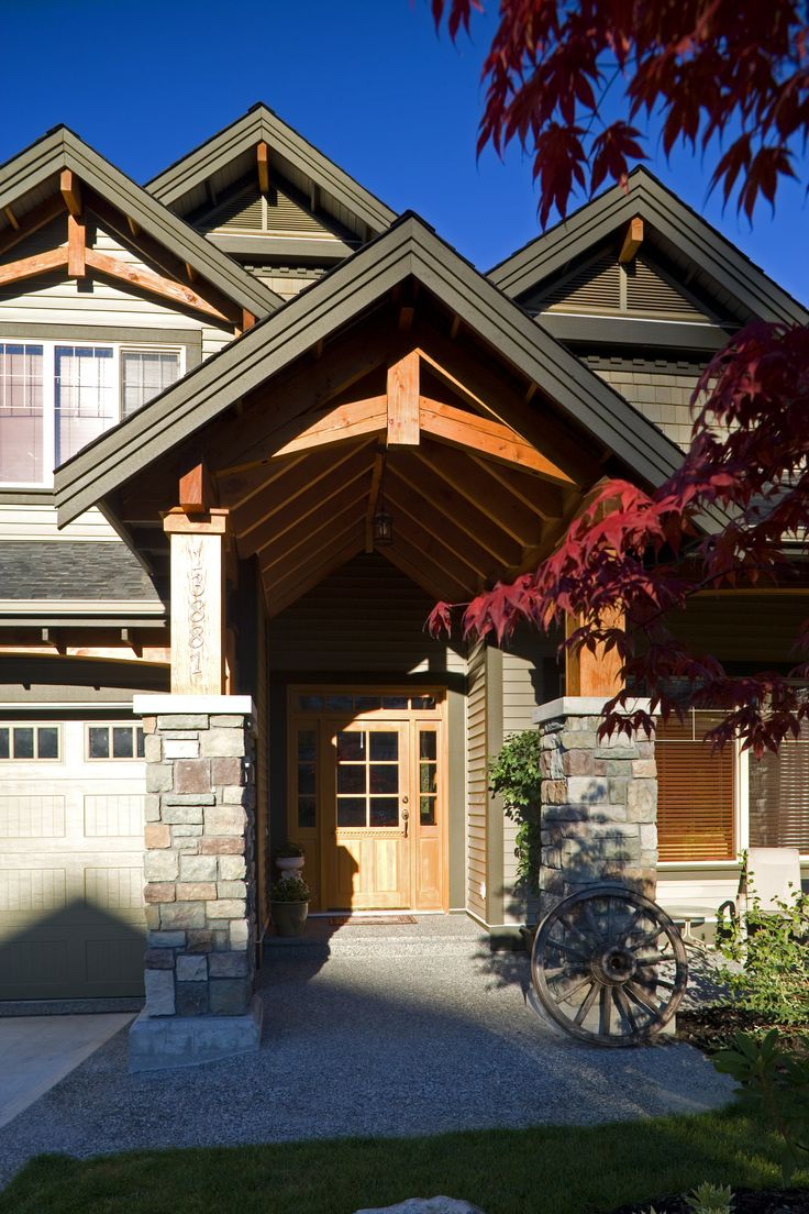 A beautiful and inviting exterior with stone columns. The stained wood rafters add character to this traditional design style. Click to get started on your next home remodeling project.