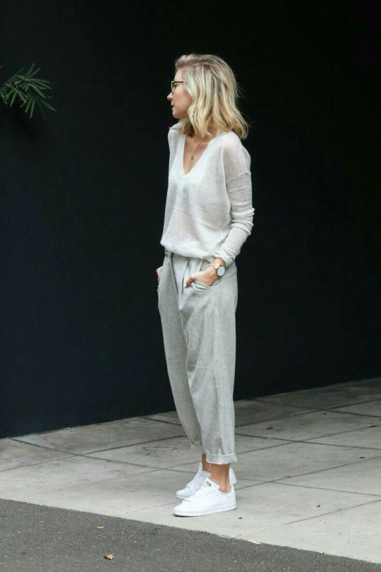Pale grey v-neck sweater. baggy pants. white athletic shoes.