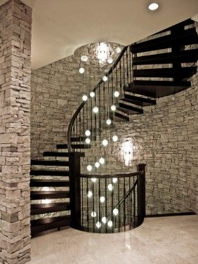 long staircase chandelier. Wonderful relief effect of exposed stone walls against wrought iron
