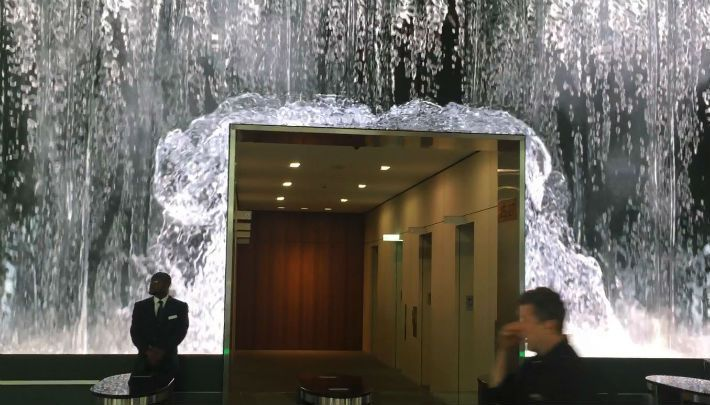 here are office building lobbies decked out in chrome and elegantly paneled wooden walls and then there is the video wall that greets visitors to Salesforce's headquarters in San Francisco.