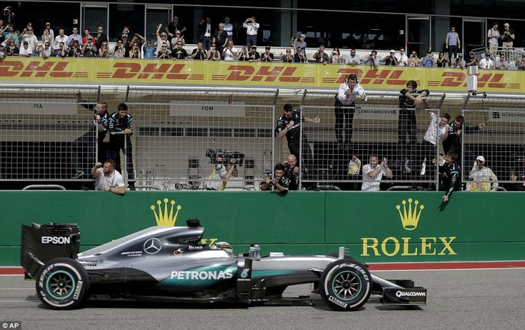 Hamilton crosses the finish line in front of Mercedes mechanics to take victory at the Uni...