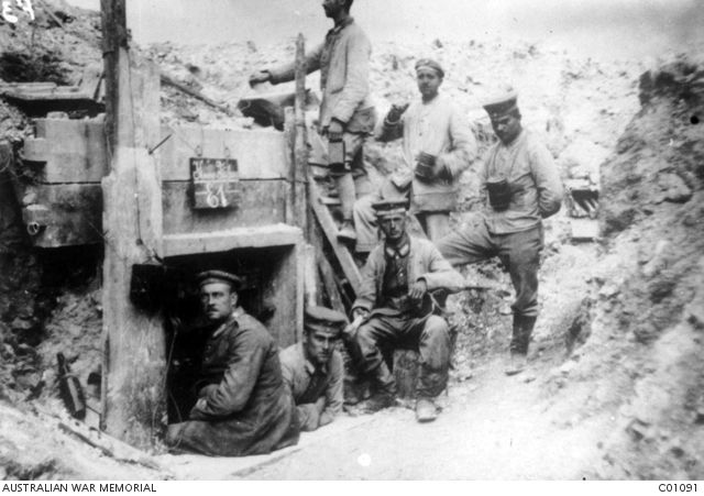 WWI, Battle of Broodseinde. A group of six unidentified German non commissioned officers (NCOs) at a dugout in a trench near the large crater where they were captured on 4 October 1917. Two of the men have mess tins, one on the far right is wearing it around his neck on a chain.