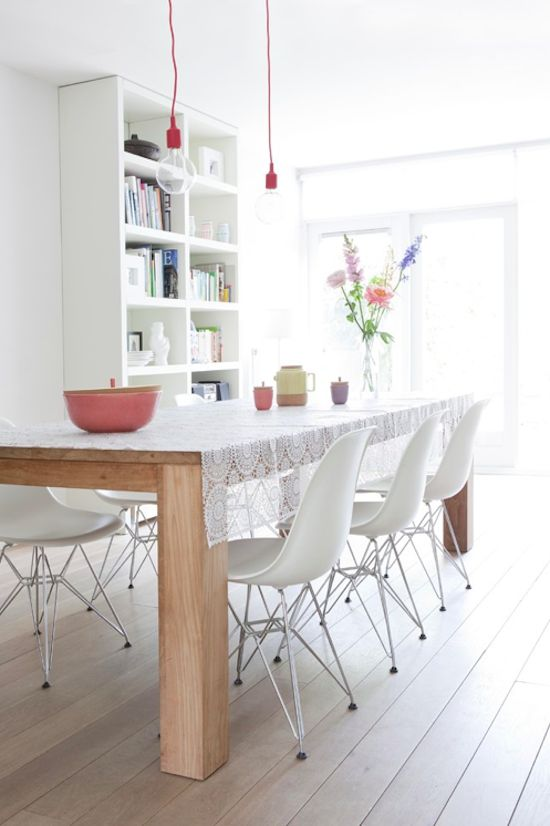 White dining room with lovely lace tablecloth. Love the shelving too.
