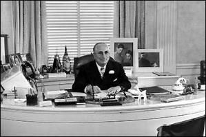 Louis B Mayer sitting at his white desk in his all white office