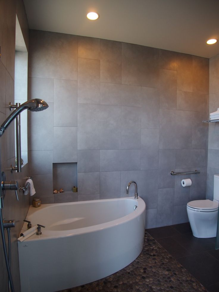 A small corner soaking tub shares a compact wet room with - Bath shower room ...