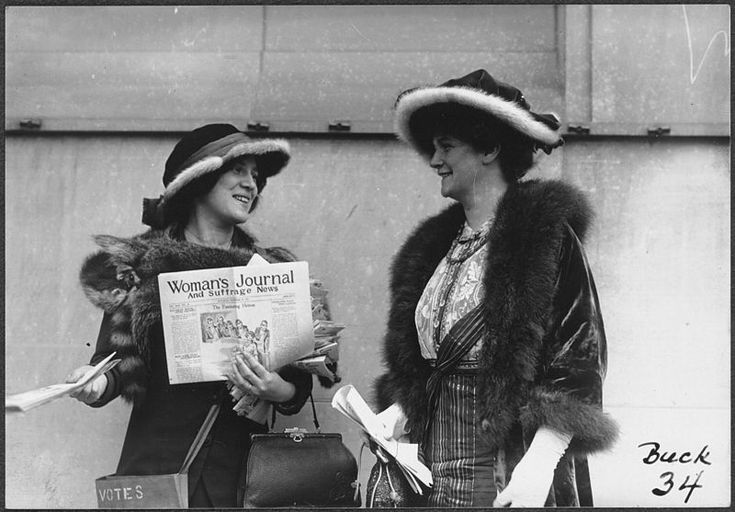 Photograph of Margaret Foley (right?) and an unidentified woman (left), both carrying pocketbooks and wearing fur-trimmed hats and fur stoles, standing outside and distributing copies of the November 29, 1913, issue of the Woman's Journal and Suffrage News. The woman on the left has a cloth satchel strapped across her body, labeled VOTES.