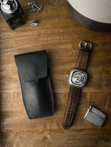 """Bas and Lokes sleek black """"Kingsford"""" handcrafted leather watch pouch. Next to it is a handsome SevenFriday watch paired with our tan """"Wylder"""" handcrafted leather watch strap. Pouch and strap are both available at www.basandlokes.com"""