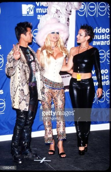 Pamela Anderson poses for a picture with two unidentified people September 9 1999 at the MTV Video Music Awards in New York City Anderson got her...