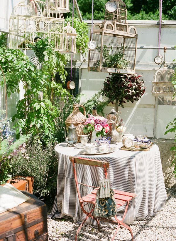 love the hanging birdcages in an outdoor garden sitting area with plants