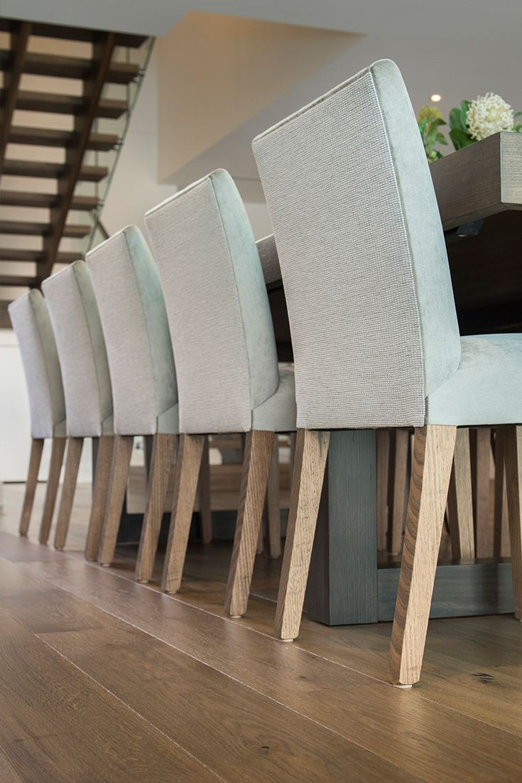 Emme Designs custom upholstered dining chairs in a neutral fabric.
