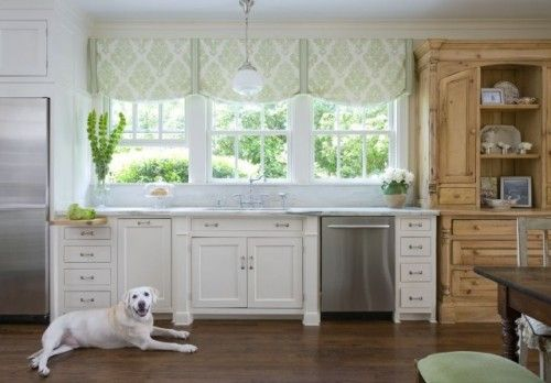 Great option for our large windows - Traditional doesn't always mean incredibly decorative. In this vintage-style farmhouse kitchen, simple roman shades fit the bill perfectly. An elegant patterned fabric creates a soft roman shade for a more casual, yet traditional window treatment, adding to the country formality of the space.