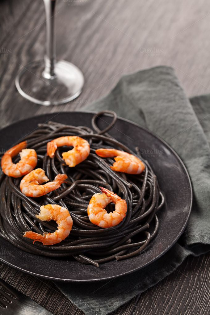 Check out Black italian pasta with shrimps food on dark background by Olha Klein on Creative Market