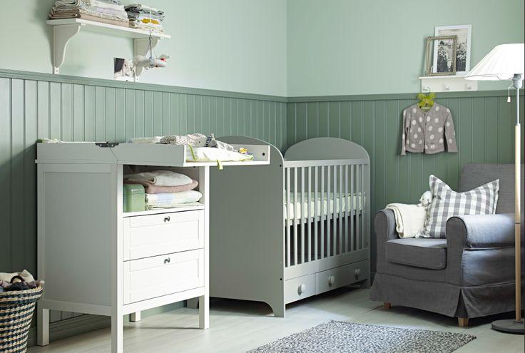 Ein Kinderzimmer mit GONATT Babybett in Hellgrau, Wickeltisch, Sessel und Teppich