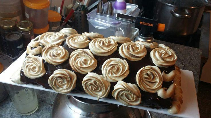 Roulé (pionono) relleno con dulce de leche y bañado en ganache de chocolate semiamargo, decorado con rosas de merengue de café