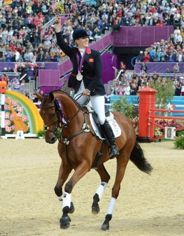 Great Britain's Zara Phillips celebrates with her Silver medal during the Team Eventing Medal ceremony on day four of the London Olympic Games as the crowds cheer her on.