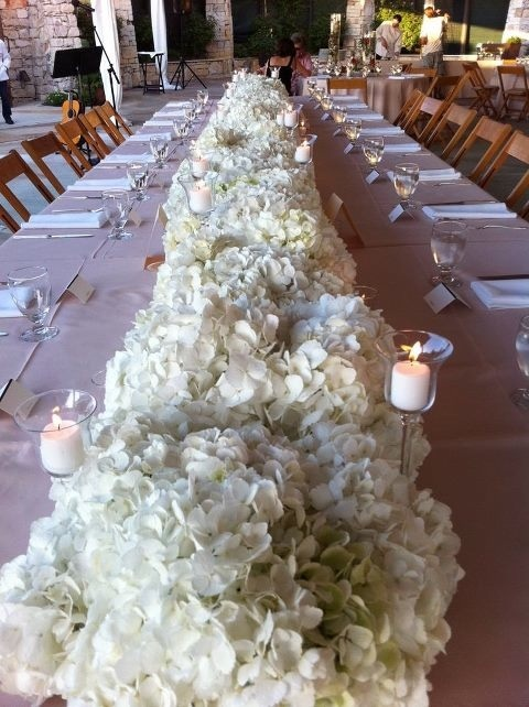 The head table will have a runner of white hydrangeas with mercury glass goblets at varied heights and mercury glass votives.