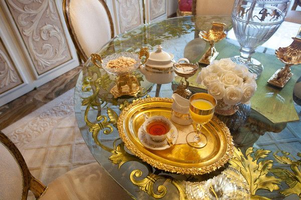 This is How Breakfast Is Served at Donald Trump's penthouse. On a glass-top dining table, tea is served on a gold platter alongside a remarkably low-key arrangement of white roses.