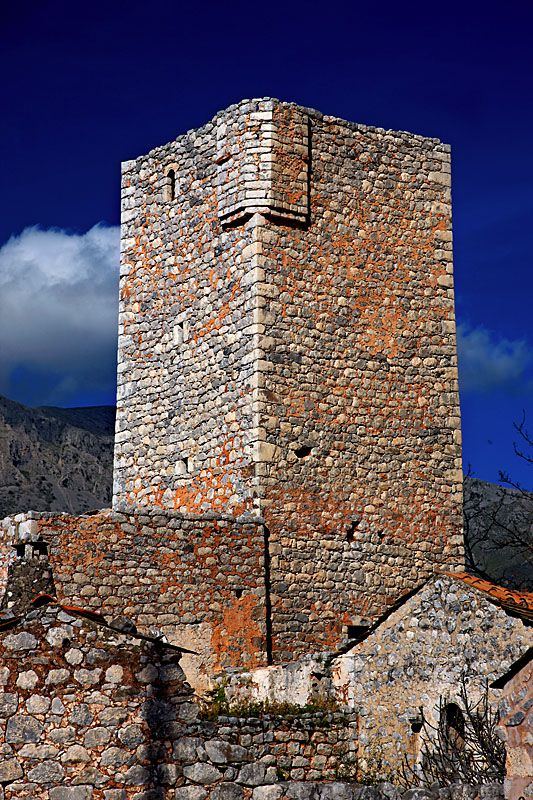 "This is a ""towerhouse"" in Haria, Mani, Greece.  Each housed a family and were 3 to 6 stories high.  They were meant to be defensive shelters, hence there were few windows, crenellations and a small door.  By the mid-19th century there were about 800 in the Mani region, and hundreds still exist today.  by Cretense"