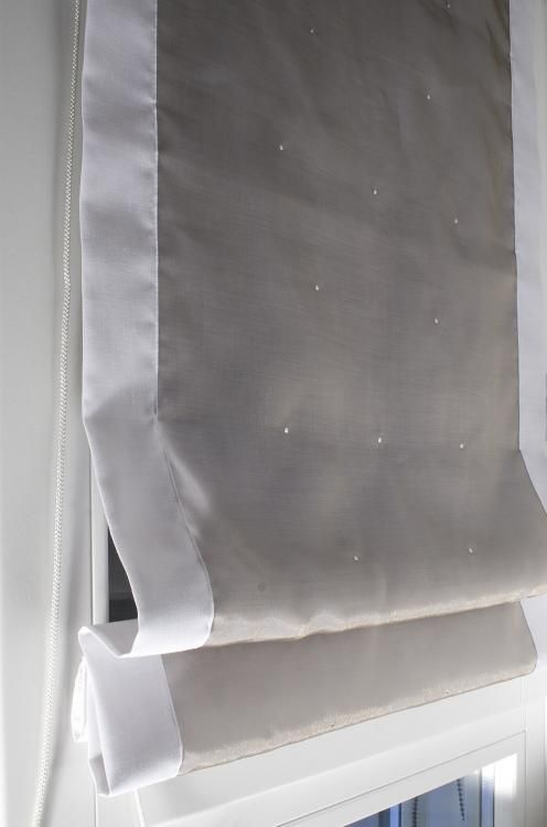 Particolare di tende a pacchetto a vetro in tessuto misto/lino bianco doppiato con organza grigio antracite mantenuta aderente tramite borchiette acciaio satinato. Realizzato da Tappezzeria Semenzato di Mestre
