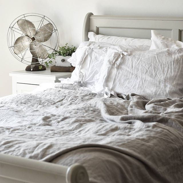 Beautiful farmhouse style bedroom. Painted sleigh bed with linen bedding and vintage fan.