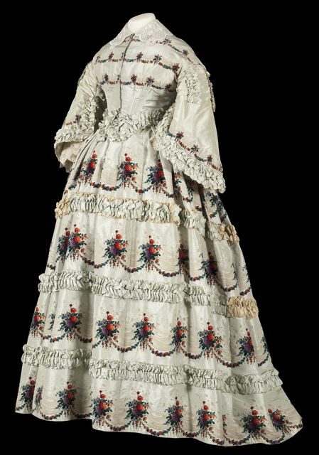 A Paris-made wedding gown of green silk taffeta with bouquets of voided velvet flowers, pleated taffeta trim and lace trimmed pagoda sleeves. Worn by a member of the Kelsey or Cowles family from Oswego County, New York, ca. 1856-1860.
