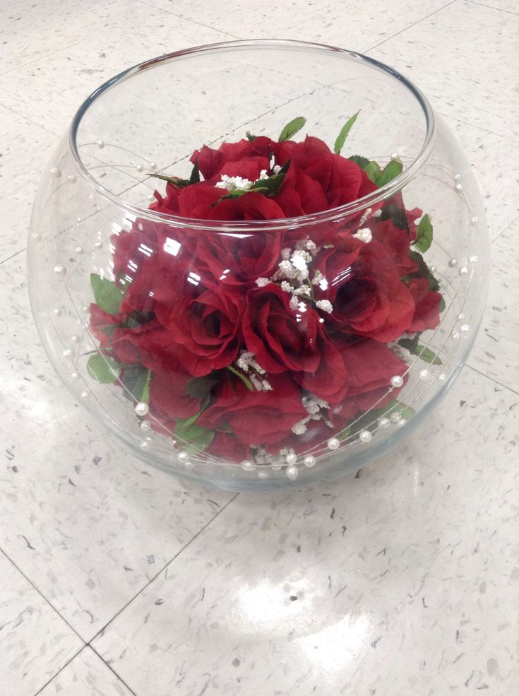 Red rose bouquet in fish bowl with white sand and pearl