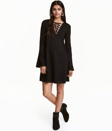 Black. Short, A-line dress in thick jersey. V-neck with lacing at top and long, trumpet sleeves.