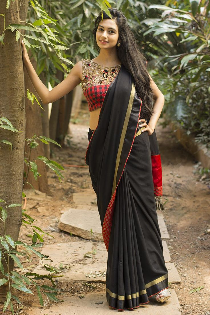 We say wow! to this amazingly interesting saree…A striking black georgette drape with surprise peekaboo red brocade bordering on the reverse side. A dual sided red detailing on the pallu amps up the charm factor. A sure fire hit this love season!Go for an intricately detailed blouse in gold black and red to knock the breath off your beau! Or tone down with a black, gold or a red blouse and remain special all the same. #houseofblouse #saree #blouse #fashion #bollywood #red #black #georgette