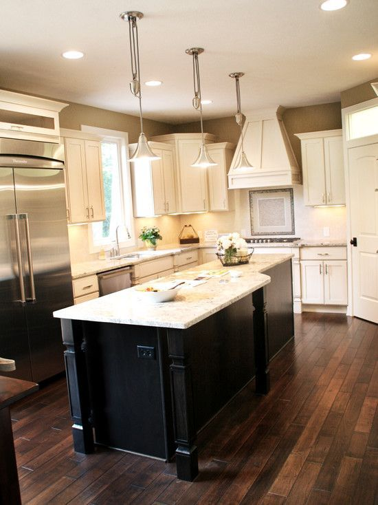 dark wood floors with cream cabinets and dark island