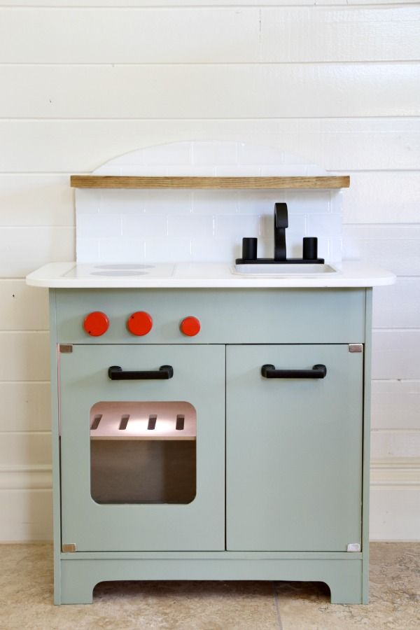 Play Kitchen Inspiration:  House tweaking's adorable hack of the Hape kitchen. Love the matte black hardware , and how the playful red knobs pop agaist the drab paint color (Sherwin-Williams coastal plain)