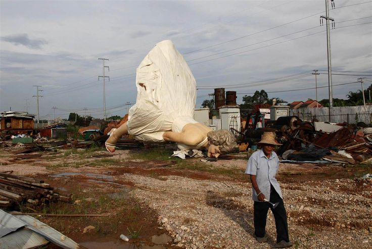 Image: Man walks past giant statue of U.S. actress Marilyn Monroe, dumped at a garbage collecting company in Guigang