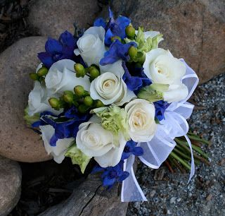 The bridesmaids wore marine blue dresses and carried petite bouquets with green roses, white fressia and navy delphinium.