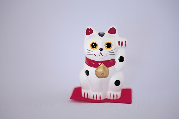 a figure of a beckoning cat, called 'manekineko'. They say it mainly brings business fortunes so you might see him at small sized business such as typical privately owned restaurants or shops. Looks so cutie but some don't. lol