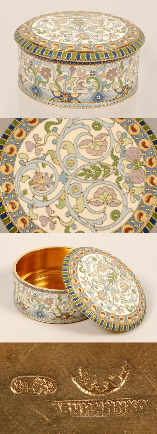 A Russian gilded silver and cloisonne enamel box, Pavel Ovchinnikov, Moscow, circa 1896-1908. The round box with cover is worked in pale wcrolling floral motifs against a cream enamel ground.