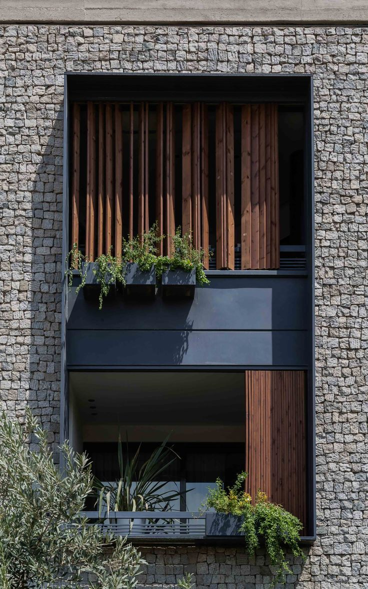 A clean, simple opening in a cladded granite stone facade that opens onto an outdoor space with adjustable wooden slats to moderate light at an Iranian apartment building. By Ali Sodagaran + Nazanin Kazerounian